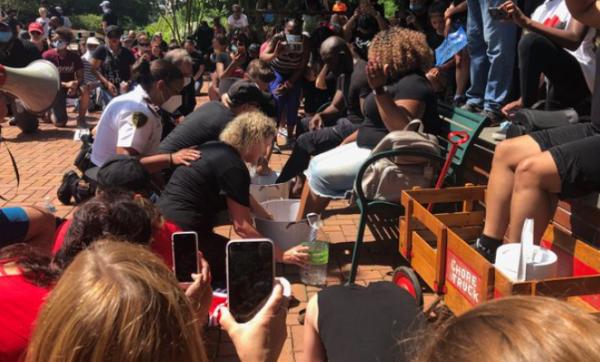 Des flics blancs et des civils s'agenouillent pour laver les pieds des manifestants noirs et implorer le pardon pendant des années de racisme